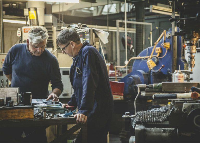 Metal gear manufacturing by men in blue